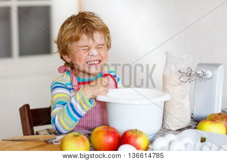 Beautiful funny blond little kid boy baking apple cake and muffins in domestic kitchen. Happy child having fun with working with mixer, flour, eggs and fruits at home.