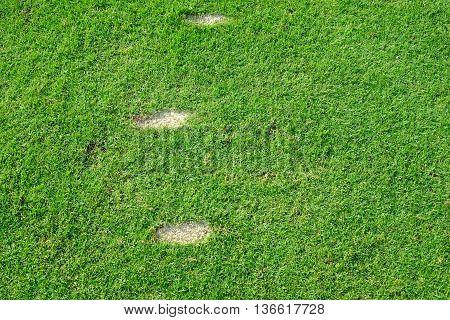 Three golf swing divot on the grass on teeing ground