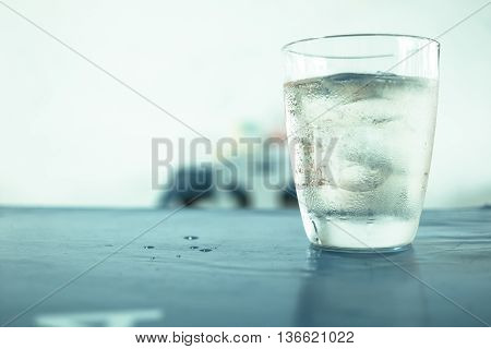 Glass of wisky soda and ice on the table