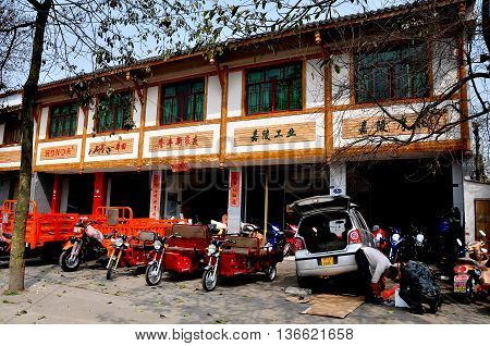 Long Feng China - March 5 2013: Mechanics working on a car at a local business specialising in the sales of motorcycle carts and trucks
