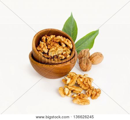 Walnut kernels isolated on white. Walnut in a wooden bowl.