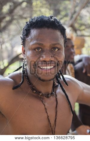 Gauteng, South Africa - July 04,  2015: Portrait of unidentified smiling African man Bantu nation with ethnic accessories and hairstyle  in Lesedi Cultural Village (unique center of African culture).