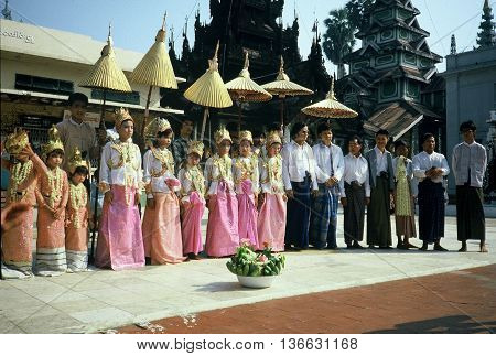 RANGOON / MYANMAR - CIRCA 1987: Girls in beautiful outfits participate in a ceremony at the Shwedagon Buddhist Pagoda in Rangoon.