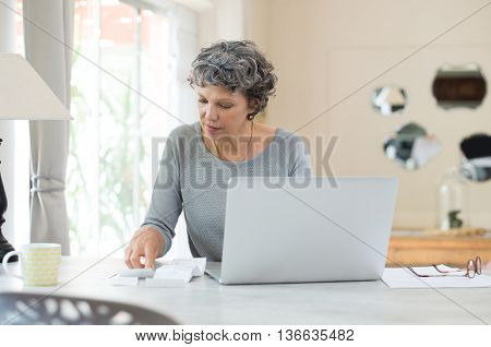 Senior woman working on home finance. Mature woman checking bills at home. Older woman checking pension approval certificate with laptop at home.