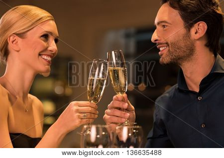 Happy young couple celebrating their marriage anniversary in a luxury restaurant. Loving couple raising a toast with champagne and looking at each other. Couple enjoying their date in a restaurant.