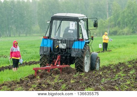 Tyumen, Russia - June 24, 2016: The 5th open championship of Russia on a plowed land. Young operator plows the site on Belarus tractor in rainy weather. Judges check quality of work