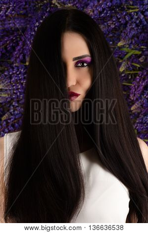 beautiful smiling woman with straight hair on background of Lupine flowers