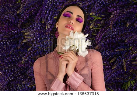 elegant lovely woman with a white peony in hands
