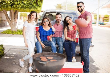 Group of good looking friends and football fands grilling hamburgers and drinking beer while tailgating at a sunday game