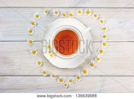 A cup of chamomile tea on the table decorated with chamomile flowers in the shape of a heart.
