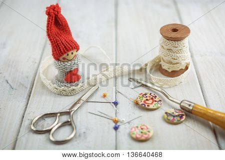 sewing tools like seam ripper, bobbin lace, pins, scissors, etcetera on wooden background