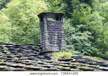 Old smoky chimney and stone roof .