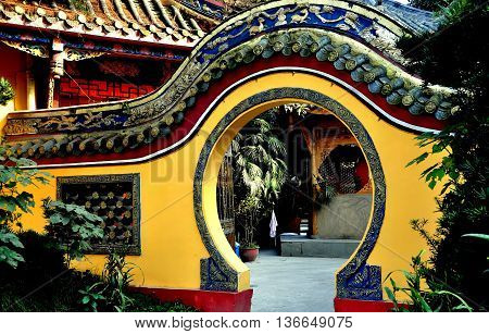 Pengzhou China - November 13 2013: A moon gate flanked by gardens leads into an inner courtyard at the Ci Ji Buddhist Temple