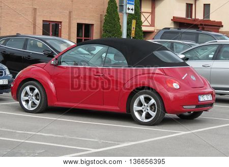 STOCKHOLM SWEDEN - CIRCA JUNE 2016: red Volkswagen New Beetle cabrio car parked in a street of the city centre