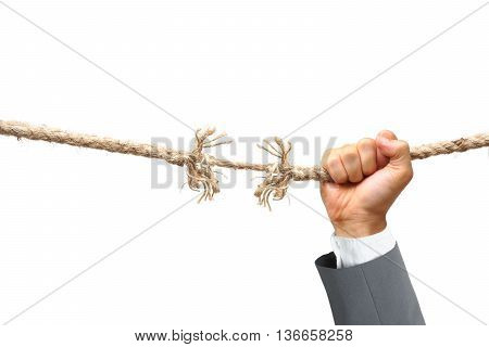 Hand of a businessman hung on almost torn apart rope - Business risk concept