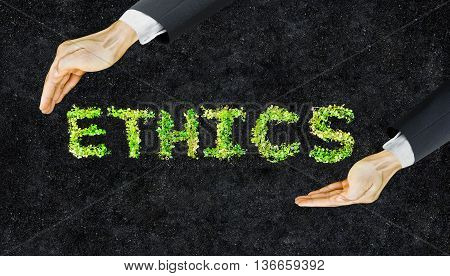 Ethics. CSR. Small green plants arranged as a word ethics with supporting hands on soil background. Corporate social responsibility. Moral behavior in business