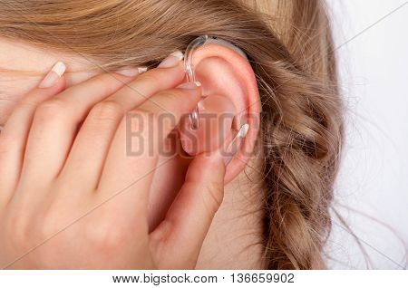 Close-up of an audiologists hand iserting a hearing aid into a young womans ear