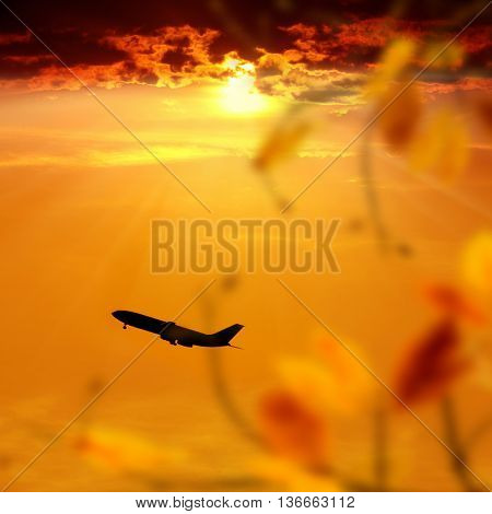 commercial airplane take off over sunset