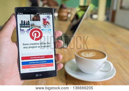 CHIANG MAI THAILAND - JUN 2016 19: A man holds LG G4 with Pinterest application on the screen. Pinterest is an online pinboard that allows people to pin their interesting things.
