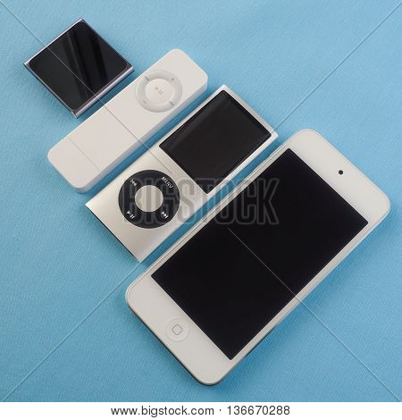 BERRY AUSTRALIA - June 20 2016 : A group of Apple iPods - iPod Nano 6th generation iPod Shuffle 1st generation iPod Touch 5th generation and iPod Nano 4th generation - on a plain blue background.