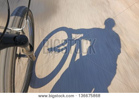Front wheel of a fast motion bike on a road with cyclist shadow