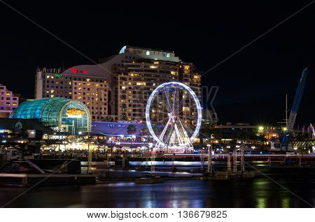 Sydney Australia - Jun 09 2016: Darling Harbour at night Pyrmont district side with shopping mall restaurants and Ferris wheel. Darling Harbour is a waterfront entertainment area