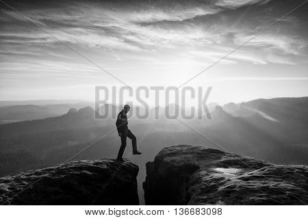 Hiker In Black Is Jumping Between Mountains Peaks.