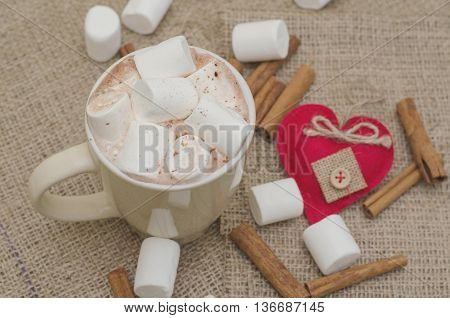 Cup of cappuccino with marshmellow and a handmade heart