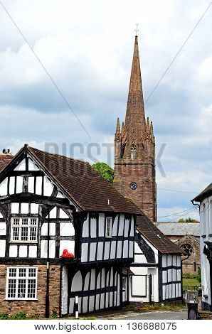View of the Red Lion in Bell Square with St Peter and St Paul church to the rear Weobley Herefordshire England UK Western Europe.