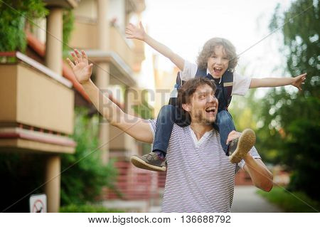 First grader sitting on the shoulders of his father. He is very happy. Father and son pretending to fly. They have a good mood.