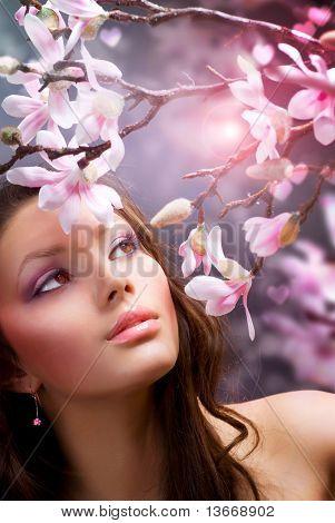 Schöne gesunde junge Frau mit Frühlingsblumen