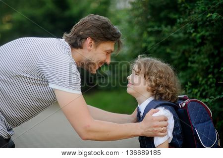 The father sees off in school of the son-first-grader. It has bent to the boy and has taken it for shoulders. The father and the son look against each other with love and smile.
