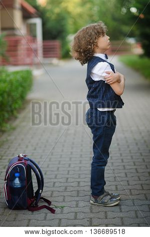 Little schoolboy stands in the school yard with an angry expression on his face . The boy crossed his arms . Student's backpack lying on the ground nearby. He does not want to go to school . Side view