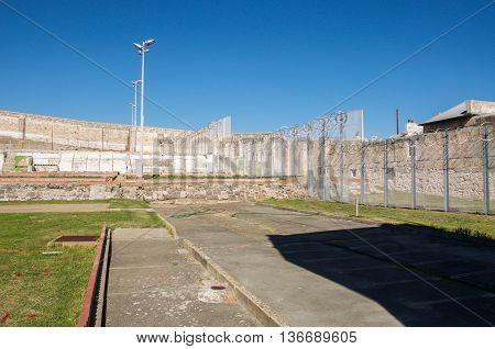 FREMANTLE,WA,AUSTRALIA-JUNE 1,2016:  Fremantle Prison with limestone boundary walls and razor wire fencing under a blue sky in Fremantle, Western Australia.
