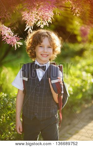 The first grader standing about beautifully blossoming bush. Sunny day. Little schoolboy smiling looking at the camera. The boy has blond curly hair and blue eyes.
