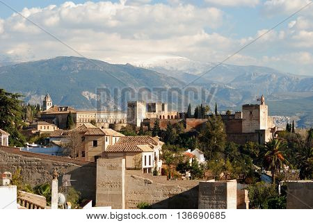 View of the Palace of Alhambra with snow capped mountains of the Sierra Nevada to the rear Granada Granada Province Andalusia Spain Western Europe.