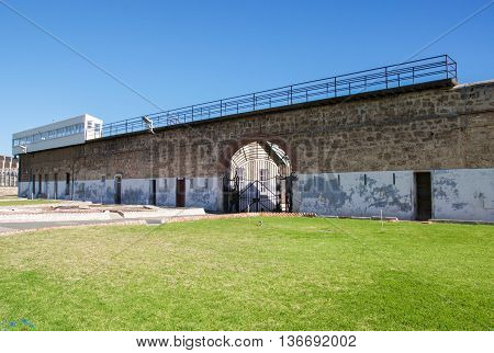 FREMANTLE,WA,AUSTRALIA-JUNE 1,2016:  Fremantle Prison wall with guard tower and arched gated entrance in Fremantle, Western Australia.