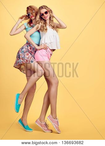 Hipsters.Fashion hipster woman in stylish summer outfit having fun. Hipster sisters friends crazy cheeky emotions.Girl in hipster fashion sunglasses,glamour hairstyle posing on yellow.Unusual creative