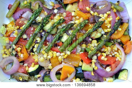 Grilled Vegetable Salad Closeup: charred asparagus, red onion, bell peppers, corn, plum tomatoes, zucchini and romaine lettuce,