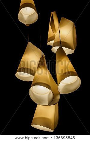 Overhanging tungsten light shades. Shades are of the inverted cone shaped format. Tungsten lighting gives the image an overall warm tone.