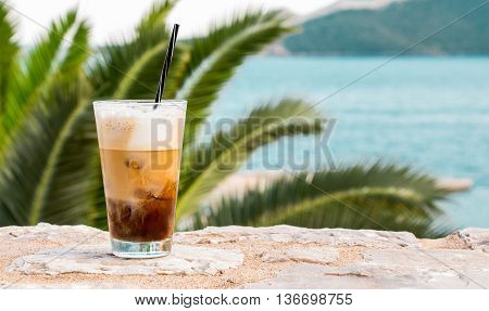 Left cup of coffee with ice cream right seascape on the background of the sea. Coffe with ice and cream. Horizontal. Daylight.