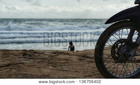 Silhouette of front wheel of motorcycle that is parked on the beach. Silhouette of woman sitting on the beach. Strong waves splashing on the seashore in blurred background.