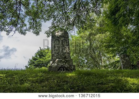 Ancient grave stone in Scottish graveyard surrounded by trees.