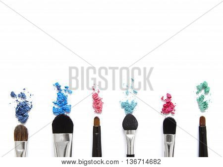 Make up brushes with loose eyeshadow pigment isolated on a white background forming a page footer