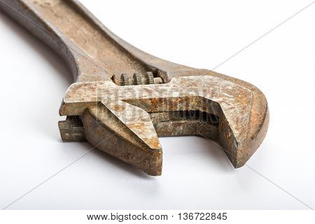 Close up of an old rusty adjustable wrench on a white back ground