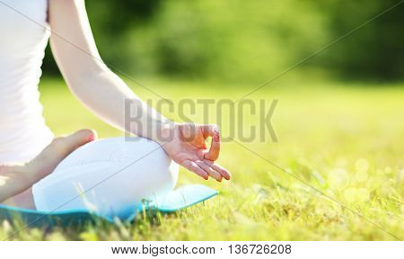 hand of a woman meditating in lotus position practicing yoga in summer