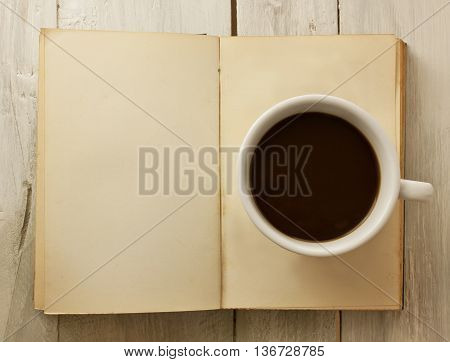 A photo of a cup of dark coffee on a page of an open old book (with copyspace) shot from above