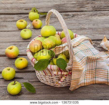 Basket with fresh apples on an old table
