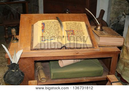 alchemist table with scrolls and with an open book
