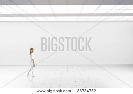 Empty big hall wall mockup. Woman walk in museum gallery with blank wall. White clear stand mock up lobby. Display artwork presentation. Art design empty floor. Expo studio wall in loft corridor.